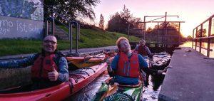 paddler der kanusportabteilung liegen, waehrend des sonnenuntergangs, mit ihren kajaks in der schleuse am warturmer stau